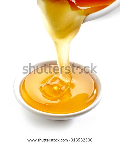 honey pouring into bowl isolated on white background - stock photo