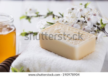 Honey spa. Bar of natural handmade soap, honey on white wooden background. Selective focus. - stock photo