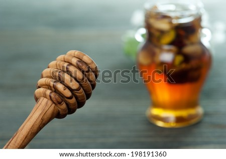 Honey spoon and jar with different nuts on a dark wooden table background - stock photo