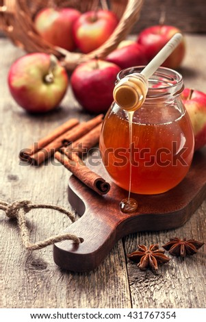 honey spoon,  jar of honey, apples and cinnamon on a wooden background in a rustic style (toning) - stock photo