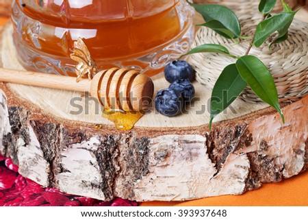 Honey spoon rural village  rustic cut down tree stump still life - stock photo