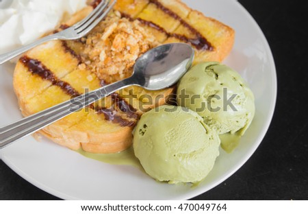 Honey toast ,green tea Ice cream and whipping cream in white plate on black background.