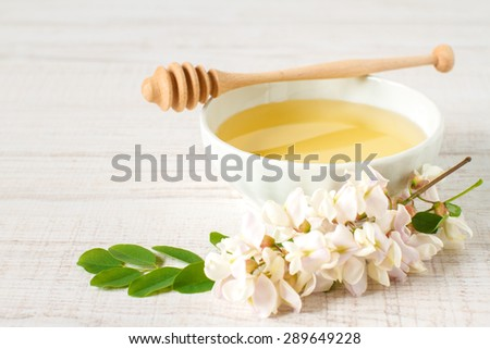 honey with acacia blossoms on a white wooden background