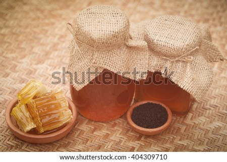 Honey with black cumin on textured surface - stock photo