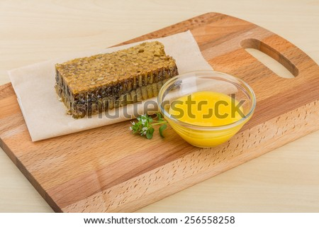 Honey with comb on the wooden background - stock photo