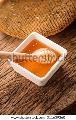 Honey with honeycomb and wooden honey dipper in ceramic bowl