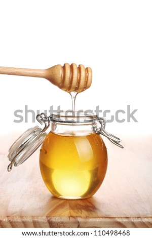 Honey with wood stick pouring. - stock photo
