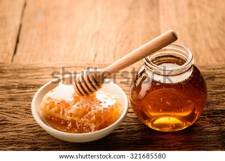 Honey with wooden honey dipper and ceramic bowl honeycomb background - stock photo