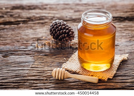 Honey with wooden honey dipper in jar on wooden table