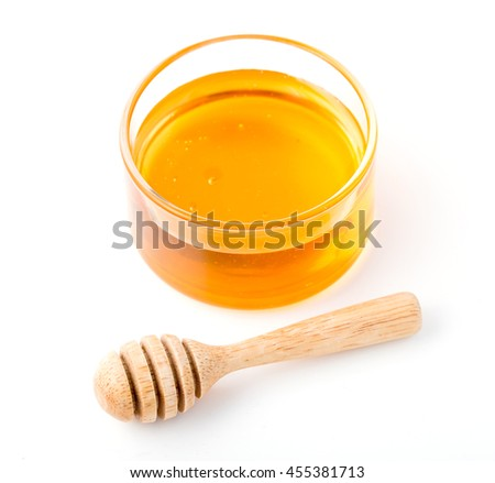 Honey with wooden honey dipper in small bowl on white background