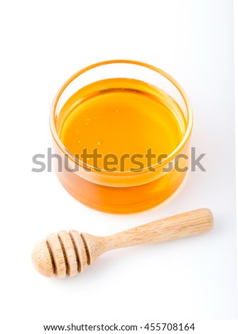 Honey with wooden honey dipper in small bowl on white background - stock photo