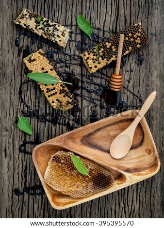 Honeycomb and honey  with peppermint ,thyme and sage set up on dark wooden background. - stock photo