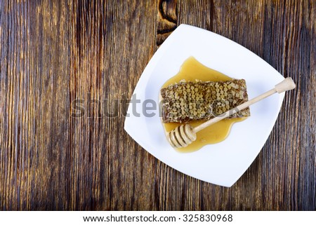 honeycomb and stick to honey on wooden background - stock photo