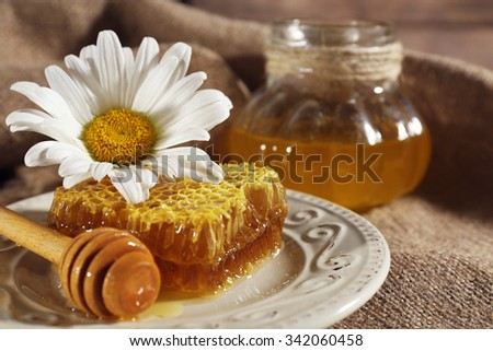 Honeycomb, dipper and chamomile on white plate and pot of honey on sacking closeup - stock photo