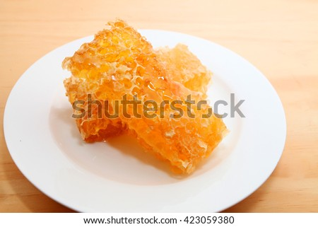 Honeycomb over wooden table background