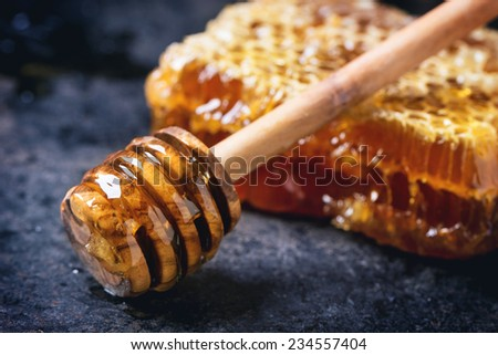 Honeycomb with honey dipper over black surface - stock photo