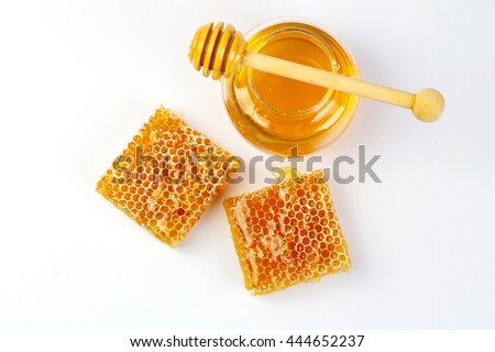 Honeycomb with jar and honey dipper isolated on white background
