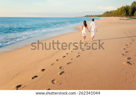 Honeymoon at the sea. Back view of loving couple walking away with footprints at sandy beach - stock photo