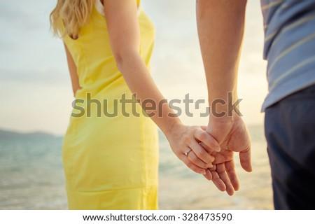 Honeymoon. Close up of loving couple holding hands on a beach near the sea. - stock photo