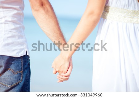 Honeymoon. Close up of loving couple holding hands on a beach near the sea.