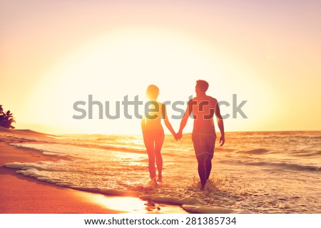 Honeymoon couple romantic in love at beach sunset. Newlywed happy young couple holding hands enjoying ocean sunset during travel holidays vacation getaway. - stock photo