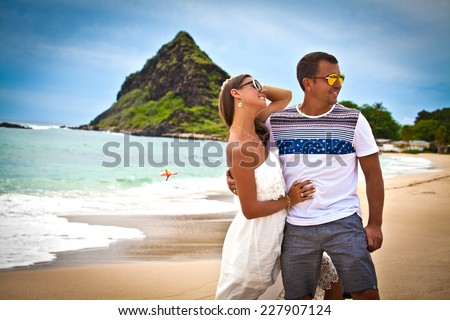 Honeymoon couple romantic in love hugging at tropical beach, Hawaii islands. Travel holidays vacation getaway.  - stock photo