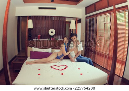 Honeymoon in hotel on tropical island, Thailand. Newlyweds on a bed - stock photo