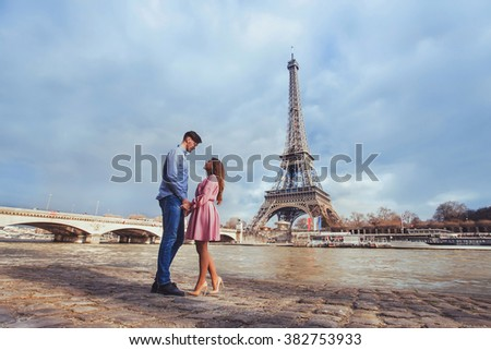honeymoon in Paris, young beautiful couple on Eiffel Tower background