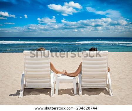 Honeymoon travel resort concept - couple in beach chairs holding hands near ocean - stock photo