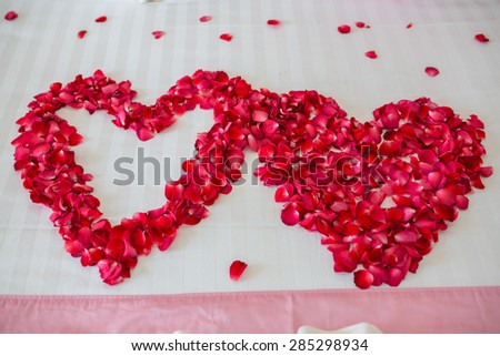 Honeymoon, Wedding bed topped with rose petals - stock photo