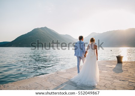 honeymoon wedding couple travel sea side. Back view. Mountains and sea background in Montenegro