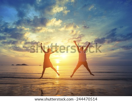 Honeymoon. Young couple jumping on the sea beach during amazing sunset. Vacation and Nature. - stock photo