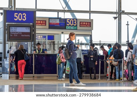 HONG KONG - APR 30, 2015: People waiting at the departure gate for boarding to flight to Shanghai in Hong Kong International airport. About 90 airlines operate flights from HKIA to over 150 cities. - stock photo