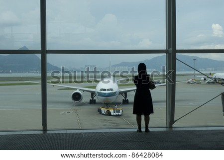 HONG KONG-AUG 24:Silhouette of a tourist takes a photo at Hong Kong International Airport in Hong Kong August 24, 2007. The airport opened for commercial operations in 1998, replacing Kai Tak airport - stock photo