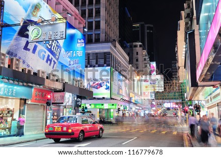 HONG KONG, CHINA - APR 23: Crowded street view at night on April 23, 2012 in Hong Kong, China. With 7M population and land mass of 1104 sq km, it is one of the most dense areas in the world. - stock photo