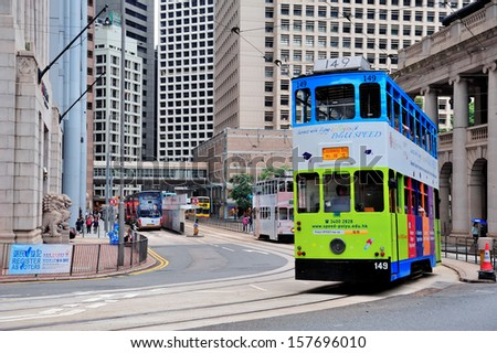 HONG KONG, CHINA - APR 23: Double-deck tram with skyscrapers on April 23, 2012 in Hong Kong, China. The Double-deck trams system in Hong Kong is one of three and the most famous in the world. - stock photo