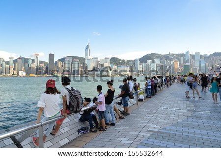 HONG KONG , CHINA - AUG. 23 : Travelers visiting the Tsim Sha Tsui Promenade (Avenue of the Stars) on Aug 23, 2013 in Hong Kong. The Avenue of Stars is located along the Victoria Harbor in Hong Kong. - stock photo