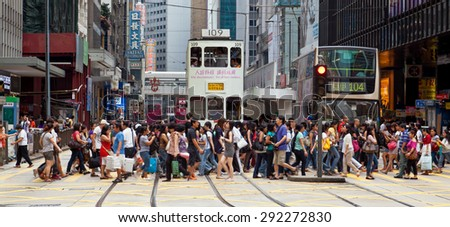 Hong Kong, China - August 21, 2011: Pedestrians crossing a busy crosswalk in Central, Hong Kong. - stock photo