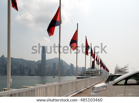 Hong Kong, CHINA - AUGUST 26, 2016: View of Hong Kong Victoria harbour, flags and buildings on August 26, 2016 from Harbour City in Tsim Sha Tsui, Kowloon side in Hong Kong.