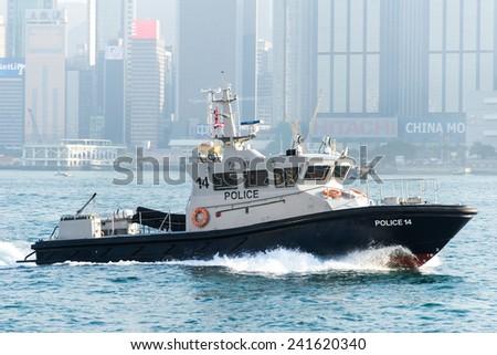 HONG KONG, CHINA - DEC. 31, 2014: Patrol boat of Hong Kong Marine Police patrols Victoria Harbour on Dec. 31, 2014 in Hong Kong, China. - stock photo