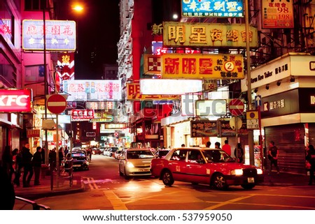 HONG KONG, CHINA - FEB 8: Billboards, bright advertisements, neon signs with hieroglyphs and cars on February 8, 2016. There are 1,223 skyscrapers in Hong Kong.