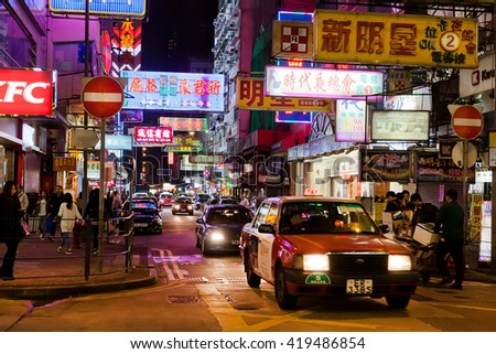 HONG KONG, CHINA - FEB 8: Billboards, bright advertisements, neon signs with hieroglyphs and taxi on February 8, 2016. There are 1,223 skyscrapers in Hong Kong.