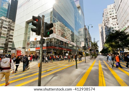 HONG KONG, CHINA - FEB 8: Crowd of people walking through the crossroad in bright light street with high modern stuctures on February 8, 2016. There are 1,223 skyscrapers in Hong Kong. - stock photo
