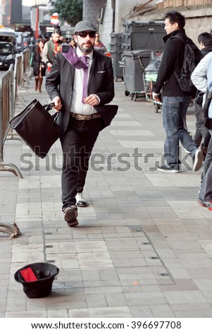 HONG KONG, CHINA - FEB 8: Mime in the role of a businessman with smiley face rushing on busy street of big asian city on February 8, 2016. There are 1,223 skyscrapers in Hong Kong.  - stock photo