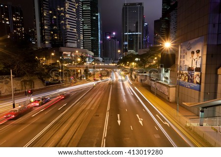 HONG KONG, CHINA - FEB 10: Night city wide streets with cars driving at crossroad with urban structures on February 10, 2016. Hong Kong dollar is the eighth most traded currency in all the world. - stock photo