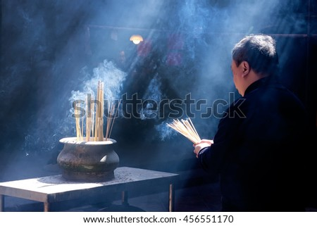 HONG KONG, CHINA - FEB 07: Old Chinese man makes a rite of prayer under the rays of light in the ancient Chinese temple on February 07, 2016. More than 47 million tourists visit Hong Kong annually