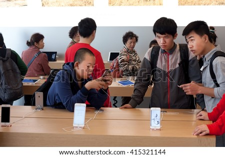 HONG KONG, CHINA - FEB 12: Unidentified children learn to use phones in the Apple store on February 12, 2016. The store sells Macintosh personal computers, software, iPod, iPad, iPhone