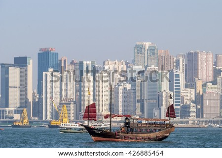 Hong Kong, China  February 07, 2010: View of Hong Kong from Kowloon with junk sailing in Victoria Harbour - stock photo