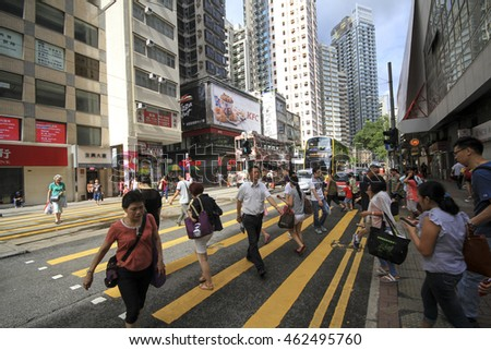 HONG KONG,CHINA, JULY 1 2016: Pedestrians rush through a very busy road in the shopping district of Causeway Bay in Hong Kong island