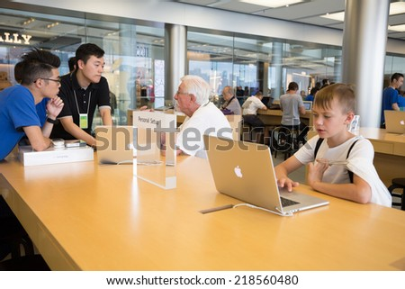 HONG KONG, CHINA - JUNE 18, 2014: Buyers and shop assistants at Apple store in Hong Kong. Store is in a shopping center IFC Mall, it is very popular with locals and tourists visiting Hong Kong. - stock photo